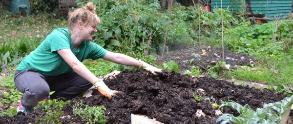 A woman in a green t-shirt gardening
